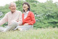 公園の芝生に座って会話をするシニアカップル 11031048177| 写真素材・ストックフォト・画像・イラスト素材|アマナイメージズ