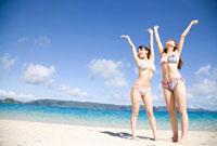 浜辺で万歳をしている水着姿の女性2人