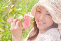 ハイビスカスの花を持って微笑む女性
