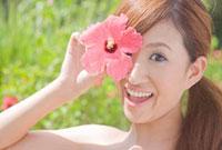 ハイビスカスの花を顔の前に持って微笑む女性