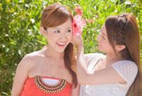 ハイビスカスの花を友人女性の頭につける女性