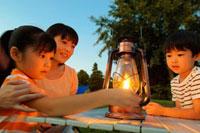 ランタンの明かりを見つめる母親と兄妹 11031048882| 写真素材・ストックフォト・画像・イラスト素材|アマナイメージズ