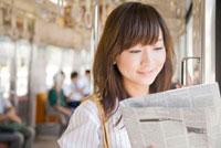 電車で新聞を読むOL