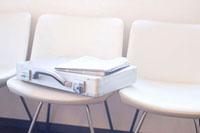 椅子に置かれたアタッシュケースと新聞