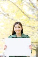 銀杏並木の下でメッセージボードを持って微笑む女性 11031050377| 写真素材・ストックフォト・画像・イラスト素材|アマナイメージズ