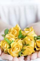両手いっぱいの黄色いバラ