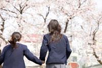 手を繋いで走る女子中学生2人の後姿