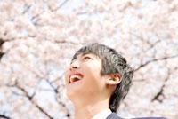 桜の下で笑っている男子中学生
