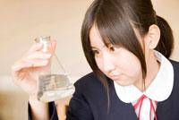 フラスコに入っている液体を見る女子中学生