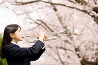 桜並木の下でトランペットを吹く女子中学生