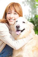 ゴールデンレトリバーを抱き寄せる笑顔の女性