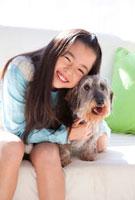 ミニチュアダックスワイヤーヘッドを抱き寄せる笑顔の女の子