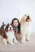 犬2匹を抱き寄せる笑顔の女の子