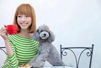 トイプードルとマグカップを持ち微笑む女性