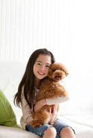 トイプードルを抱きしめ微笑む女の子