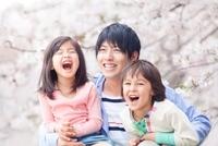 桜の下で微笑む親子