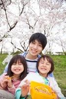 桜の下でお弁当を食べる親子