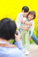 菜の花畑で父親に記念撮影をしてもらう母親と息子