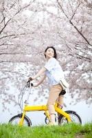 桜の下で自転車に乗って振り返る笑顔の女性