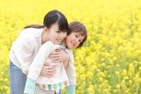 菜の花畑で男の子を抱きしめる母親