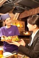 女性客に料理を渡す居酒屋店員