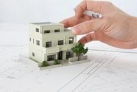 住宅模型に添えられた男性の手