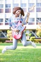 ギターを持ってジャンプする女子大学生