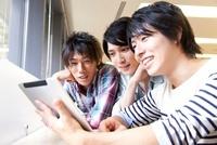 タブレットPCを見る男子大学生
