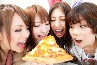 ピザにかじりつく女性達