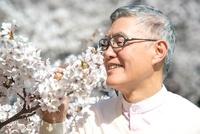 桜の香りをかぐシニア男性