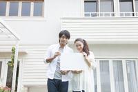 メッセージボードを持って家の前で微笑む夫婦