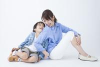 背中を合わせて笑う母子