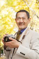 カメラを持って微笑むシニア男性