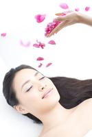 仰向けに横になっている女性とバラの花びら