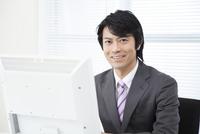 PCの前で微笑むビジネスマン 11031088196| 写真素材・ストックフォト・画像・イラスト素材|アマナイメージズ