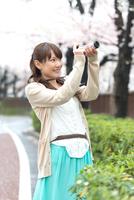 桜を撮影しに出かける女性