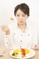 人参を食べることに躊躇する女性 11031092127| 写真素材・ストックフォト・画像・イラスト素材|アマナイメージズ