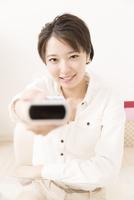 テレビのリモコンを操作する女性 11031092131| 写真素材・ストックフォト・画像・イラスト素材|アマナイメージズ