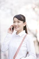 桜並木の下で電話をする女性