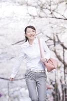 桜並木の下を走る女性