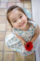 オレンジ色のガーベラを持つ女の子