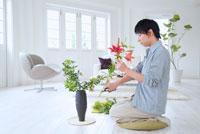 リビングで生け花をする日本人男性