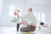 リビングで生け花をする日本人シニア男性