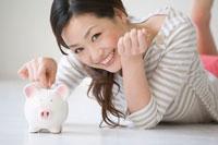 コインを貯金箱に入れる女性 11032003783| 写真素材・ストックフォト・画像・イラスト素材|アマナイメージズ