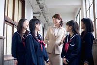 廊下で話をする先生と女子中学生4人