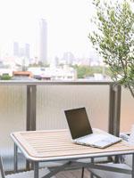 テーブルの上のパソコンと都内の街並