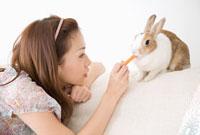 ウサギに餌をやる女性