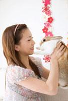 ウサギを抱き上げる女性 11032005390| 写真素材・ストックフォト・画像・イラスト素材|アマナイメージズ