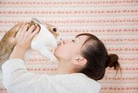 ウサギを抱き上げる女性