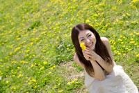 タンポポを持った笑顔の女性